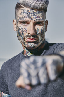 Portrait of tattooed young man outdoors clenching his fist - ZEDF01461
