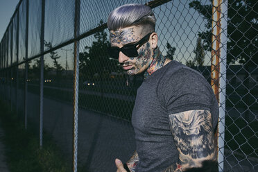 Tattooed young man at wire mesh fence wearing sunglasses - ZEDF01464