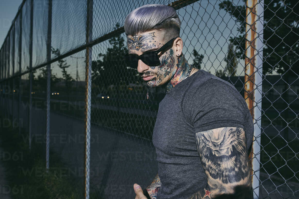 Tattooed young man at wire mesh fence wearing sunglasses - ZEDF01464 - Zeljko Dangubic/Westend61