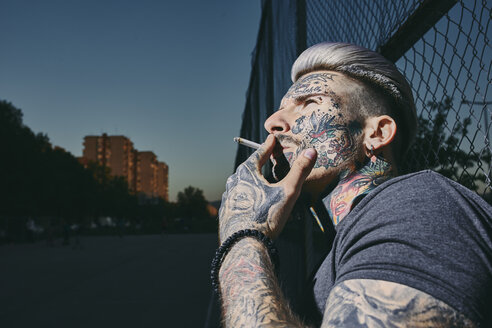 Portrait of tattooed young man smoking a cigarette at wire mesh fence - ZEDF01467
