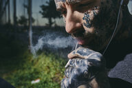 Close-up of tattooed young man with earbuds smoking a cigarette - ZEDF01470