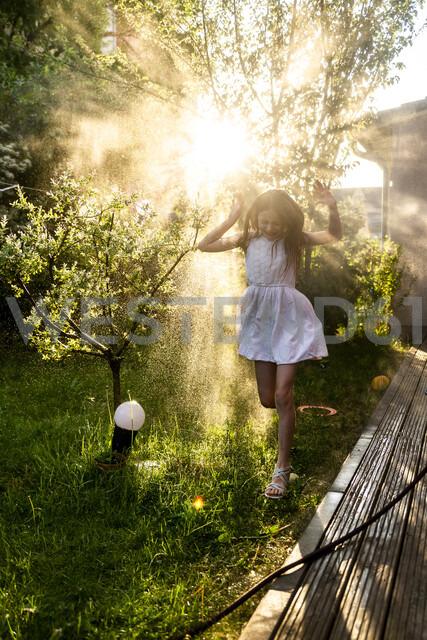 Girl having fun with garden hose in summer - SARF03735