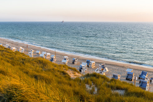 Germany, Schleswig-Holstein, Sylt, beach and empty hooded beach chairs at sunset - EGBF00249