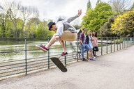 Young male skateboarder doing jump trick for friends in Battersea Park - CUF04835