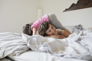 Mother and daughter playing on bed, daughter clambering over mother - ISF01253