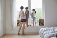 Mother, son and daughter looking out of bedroom window, rear view - ISF01259