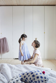 Mother and daughter in bedroom, face to face, mother wearing crown headband - ISF01262