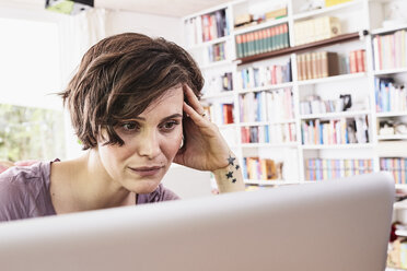 Mid adult woman at home, using laptop, worried expression - ISF01271