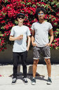 Friends standing next to each other beside red bougainvilleas - ISF01292