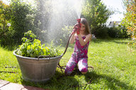 Girl with garden hose in summer - SARF03741