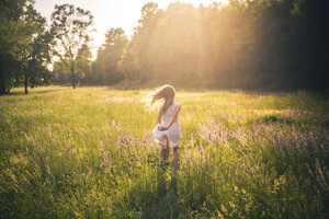 Back view of girl running on flower meadow at evening twilight - SARF03744
