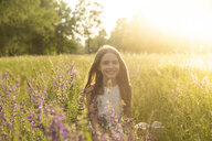 Portrait of smiling girl crouching on flower meadow at evening twilight - SARF03747
