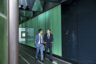 Businessmen walking through modern glass building, London, UK - CUF04910