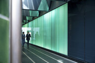 Businessmen walking through modern glass building, London, UK - CUF04913