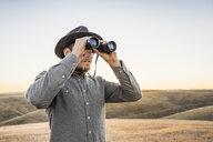 Man looking through binoculars at rolling prairie hills, Bakersfield, California, USA - CUF04928