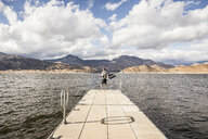 Rear view of man looking out from windy pier on Lake Isabella, California, USA - CUF04931