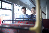 Two businessmen looking at smartphone on double decker bus - CUF04934