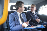 Two businessmen discussing paperwork in taxi cab - CUF04943