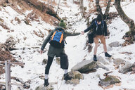 Man hiking in snowy forest giving girlfriend a helping hand, Monte San Primo, Italy - CUF04988