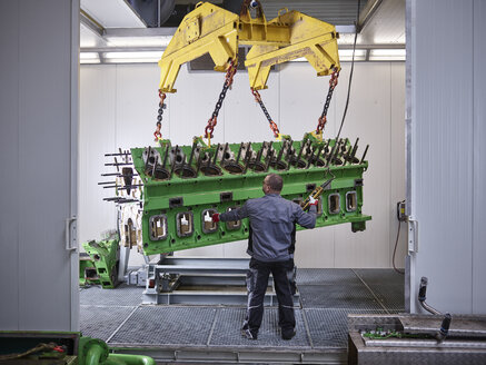 Worker in factory lifting engine block with crane - CVF00516