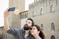Couple taking smartphone selfie by Arezzo Cathedral, Arezzo, Tuscany, Italy - CUF05157