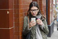 Young woman outside subway station looking at smartphone - CUF05172