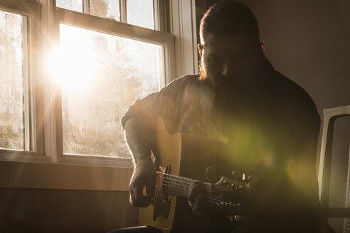 Man playing guitar beside window - CUF05289