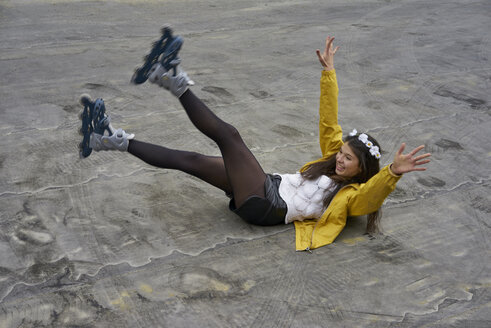 Smiling woman with inline skates falling on ground - BEF00048