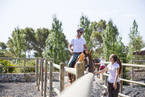 Female groom leading horse rider in paddock at rural stables - CUF05421
