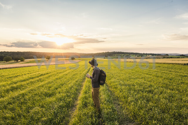 Mid adult man, standing in field, holding SLR camera, looking at view, Neulingen, Baden-Württemberg, Germany - CUF05475 - Manuel Sulzer/Westend61