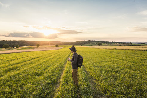 Mid adult man, standing in field, holding SLR camera, looking at view, Neulingen, Baden-Württemberg, Germany - CUF05475