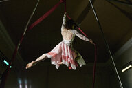 Low angle rear view of young female aerial acrobat hanging from silk rope - CUF05508