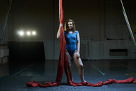 Portrait of young female aerial acrobat holding red silk rope - CUF05511