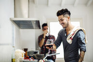 Male couple preparing meal in kitchen, drinking wine - CUF05550