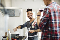 Male couple preparing meal together in kitchen, drinking wine - CUF05553