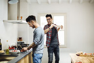 Male couple preparing meal together in kitchen, fooling around - CUF05556