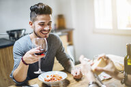 Male couple enjoying meal together, grating parmesan cheese on pasta, drinking wine - CUF05559