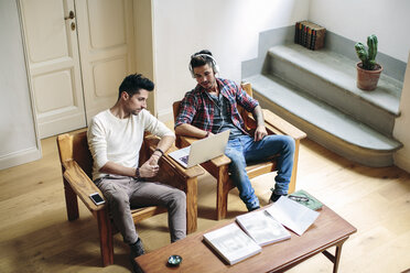 Male couple sitting down at home, looking at laptop - CUF05583