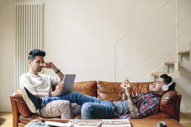 Male couple relaxing on sofa, wearing headphones, using smartphone and laptop - CUF05586