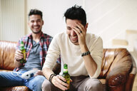 Male couple sitting on sofa, holding beer bottles, laughing - CUF05589