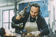 Male metalworker hammering metal in forge workshop - CUF05628