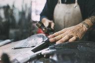 Hands of metalworker hammering lead metal in forge workshop - CUF05667