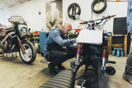 Mature man, working on motorcycle in garage - CUF05688