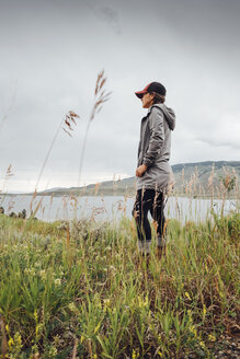 Young woman standing near Dillon Reservoir, looking at view,, Silverthorne, Colorado, USA - ISF01335