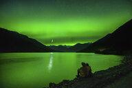 Couple sitting beside Lillooet Lake, watching northern lights, Pemberton, British Columbia, Canada - ISF01365
