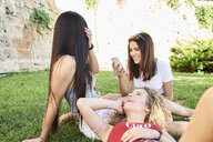 Three young women relaxing in a park using cell phones and listening to music - IGGF00472