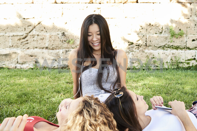 Three young women relaxing in a park listening to music - IGGF00475