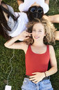 Portrait of young woman lying in grass with friends listening to music - IGGF00478