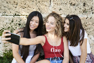 Three smiling young women sitting at stone wall taking a selfie - IGGF00481
