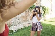 Spain, Mallorca, Palma, young woman taking picture of friend in a park - IGGF00484